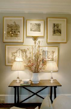 Sophisticated foyer design with iron and rustic wood trestle console table, glass column lamps with pleated linen shades, white porcelain pitcher vase, gilt gold frames art gallery and soft gray walls paint color. white gold brown gray entrance foyer colors.