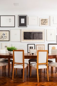 A gallery wall and dining set look super sleek in mixed neutrals. Tour more of Alison Cayne's Stunning West Village Townhouse on our Style Blog!