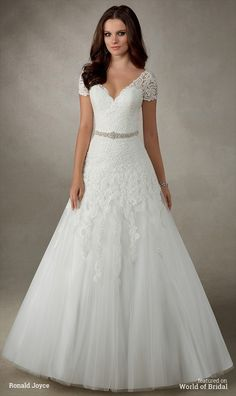 A unique capped sleeved A-line dress with lace appliques and beautiful crystal waistband