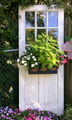 vieille porte blanche transformée en support pour jardinière dans le jardin