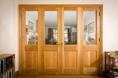 Bespoke oak internal room dividing doors with a natural finish.   Clear glass to allow light and brass door furniture