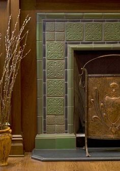 Designer Carisa Mahnken used decos of two sizes with a contrasting liner and a relief border in this custom surround made with Motawi tiles.