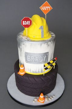construction first birthday party cake with hard hat topper, road signs and tire layer