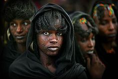 Wodaabe women with tattooed faces, Lake Chad area, Niger, Africa. I love how the focus is specifically on her, with the women in the back blurred just so.