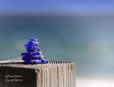 Blue Sea Glass Beach Cairn Photo- Deep Blues, Calming Art. Blue Cairn #2 Beach Photo- This small, blue cairn stands tall on the rail- a simple symbol of our journey through life; a journey that we take one step at a time. Just like stacking the glass one piece at a time, we build on what was before. To me, this cairn represents the need to keep life in balance. This particular cairn is small on the rail- the vivid cobalt blue colored glass a bright beacon overlooking the beach. The image…