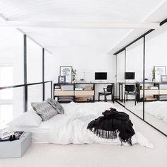 White Scandinavian loft bedroom   I have always believed a light and white room needs a good dose of black and I guess the bedroom in this loft in no exception. The mirror doors beautifully reflect the huge amount of light coming through the industrial glass wall, while a small amount of green and natural coloured wooden drawers add a little warmth to the room ☆ more on http:vosgesparis.com