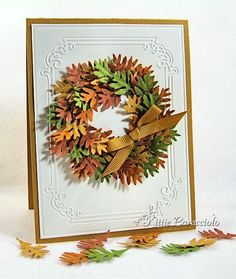 die cut a ring with Nestabilities to act as the base and a guide for my wreath. punch out several leaves in mustard, rust, olive and pumpkin and alternately attached them to the ring using Glossy Accents.
