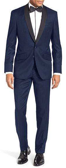 This slim-fit navy blue tuxedo features a shawl collar and two-button jacket