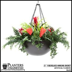 Artificial fern and bromeliad in a black hanging basket