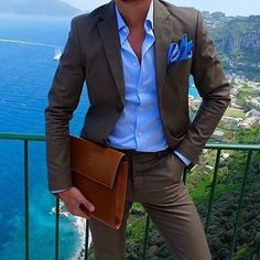 Shop this look on Lookastic: https://lookastic.com/men/looks/dark-brown-suit-blue-dress-shirt-tobacco-zip-pouch/19816   — Blue Pocket Square  — Blue Dress Shirt  — Dark Brown Suit  — Tobacco Leather Zip Pouch