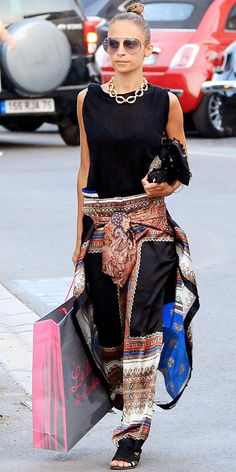 NICOLE RICHIE In Saint-Tropez, France, Richie was spotted in a black sleeveless top and printed wide-leg pants with a matching top tied around her waist. She completed her vacation look with aviators, black sandals, a printed purse and a chunky gold chain necklace.