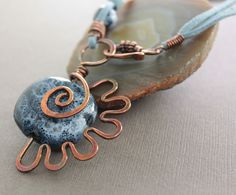 swirly flower copper necklace with denim blue porcelain bead on blue leather cord