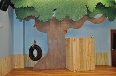 This is a puppet stage. Love the tire swing and the boards on the wall as a porch.