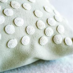 Bead disc embroidered onto scatter cushion.