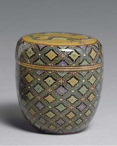 A Cloisonné Enamel Tea Caddy Meiji period (19th century), signed Kyoto Namikawa [workshop of Namikawa Yasuyuki, 1845-1927] Designed in colored enamels and worked in silver wires on the cover with a circular panel of a coiling dragon on a mustard-yellow ground, the sides of the cover and body designed in gilt wire with a floral diaper pattern, the mounts gilt metal; signed on a silver tablet mounted on base 2 5/8in. (6.8cm.) high