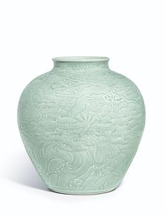 A MAGNIFICENT CARVED CELADON-GLAZED 'DRAGON' JAR, SEAL MARK AND PERIOD OF QIANLONG. Superbly potted with a generous well-rounded ovoid body, crisply carved in varying levels of relief with a wondrous scene of two five-clawed dragons, writhing ferociously through flames and clouds, all above a turbulent sea, the whole surface superbly applied with an exquisite clear watery blue-green glaze, skilfully transmuting to a white on the outlines of the dragons and clouds. Six-character seal mark.
