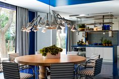 A modern kitchen with blue details and plants. #decor #casacor #blue #interior #design #modern #casadevalentina