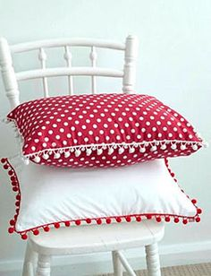 Red and white pillows with pom pom trim.