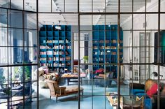 """""""The Madrid home of Jaime Lacasa, founder of the stylish clothing and furnishings shops Jimmy's and Jimmy's Scooter, is divided in two by a large paned glass wall. Photo by P. Zuloaga & I. Semenat."""""""