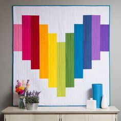Piece of My Heart Strip Quilt Free Pattern Download-This is a fun wall or lap quilt pattern for beginners that involves simple straight sewing! This quilt can be finished fairly quickly. With this rainbow heart quilt pattern in your digital collection, you'll always have a modern, go-to project. Finished size is 55″ x 55″.