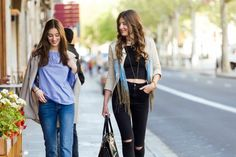 Two beautiful young women walking and talking in the street. Free Photo