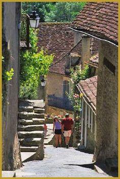 Photo des visiteurs dans le coeur historique de la cité médiévale classée de Limeuil dominée par les belles maisons périgourdines en pierres, dans la rue du Port. Visiter Limeuil, photos des plus beaux villages de France.