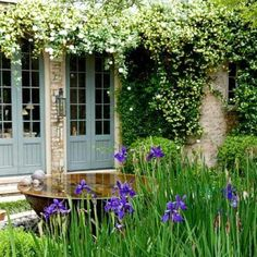 The cottage journal - LOVE these blue doors and pale stone walls. The bronze water bowl and beautiful irises are just too perfect...
