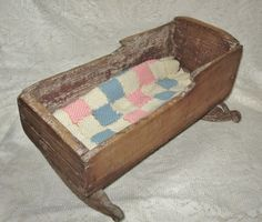 19th century primitive doll cradle with coverlet. SOLD