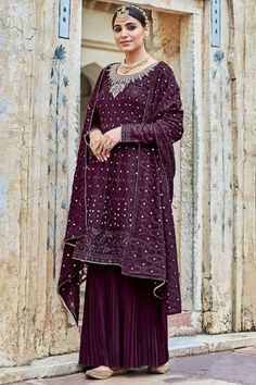 Exquisitely embroidered with traditional design, this plum purple georgette sharara suit which comprises delightful traditional look. This round neck and full sleeve wedding wear suit designed using resham, thread and silver zari work. Accompanied by a matching georgette sharara pants in plum purple color with burgundy maroon georgette dupatta. Sharara pants is plain. #shararasuits #malaysia #Indianwear #weddingwear #andaazfashion Indian Attire, Indian Wear, Garara Suit, Wedding Mint Green, Pantalon Cigarette, Plum Purple, Burgundy, Georgette Fabric, Costume