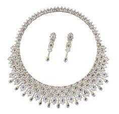 Collana a bavaglio formata da rosoni in oro bianco e brillanti e da castoni a goccia in oro bianco incassati diamanti taglio rosa, accompagnata ad un paio di orecchini pendenti con rosone in oro bianco e brillante e, al centro, castone ovale in oro bianco con diamante coroné. Per la collana: 409 diamanti tondi taglio brillante ct. 6,24 76 diamanti taglio rosa ct. 18,54 14 diamanti taglio rosa ct. 4,18 13 diamanti ct. 17,05 Per gli orecchini: 30 diamanti tondi taglio brillante