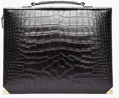 """ALEXANDER WANG. Black rectangular portfolio leather case in black with embossed reptile print throughout. Gold tone hardware. Metal bumpers at corners. Single carry handle at top. Zip closure at main compartment. Card slots, document holder, pen holders and cell phone pocket at interior, with elasticized iPad compartment under main flap. Lined. Approx 10"""" depth x 13.2"""" length x 1.7"""" width. 100% leather."""
