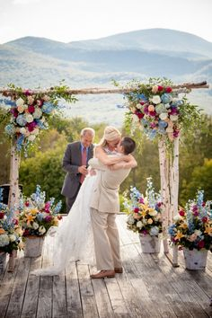 Bride and groom have first kiss under pink, blue and white flowers by Kathleen Landwehlre Photography