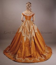 Orange evening dress with white embroidery. Attributed to Charles Frederick Worth, ca . 1865-67. Silk rib weave ground, silk netting, silk thread. Embroidery type: whitework Back view