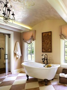 Inspired by a French countryside chateau, this bathroom is cloaked in elegant shades of beige and white with a luxurious freestanding tub clad with wrought-iron fixtures. A vaulted ceiling with gold-leaf detail adds even more drama.
