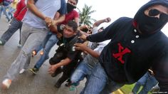 Demonstrators in Mexico hold a riot policeman during a protest against the suspected massacre of 43 missing students