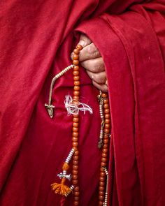 "Pictured is a Bhutanese holding prayer beads or ""mala"". These beads are viewed as powerful and are inseparable from one's personal yidam. I chose this because it is important to the Bhutanese and their culture."