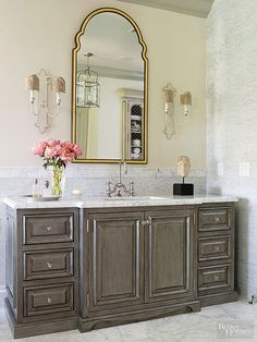 European-inspired bathrooms benefit from distinctive sconces bearing an antiquated air. With prettily profiled bases, gold-trimmed fabric shades, and gray-toned details, these sconces beautifully harmonize with this bathroom's marble surfaces and glazed cabinet finishes.