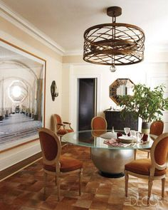 An Hervé Van der Straeten chandelier is suspended above a 1988 Italian table in the dining room; the Maison Jansen chairs are upholstered in an Edelman suede, and the photograph is by Candida Höfer.