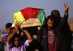 A Turkish Kurd shows the victory sign as he carries a coffin during the funeral of three Kurdish fighters killed during clashes against Islamic State in Syrian town of Kobani, at a cemetery in the southeastern town of Suruc, Sanliurfa province October 23, 2014. REUTERS-Kai Pfaffenbach