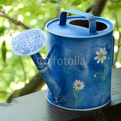 blue watering can with a painted daisies