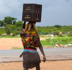 Africa   Mwila Woman Carrying Beer Crates On Her Head And A Baby On Her Back.  Chibia Area, Angola   © Eric Lafforgue