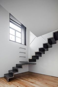 Inviting slim cantilevered staircase with an interesting overlapping rest landing detail and wall mounted rungs for making a quick escape out of the window!