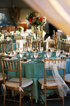 reception tabletop details - aqua colored table cloths with gold chairs