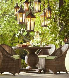 With a cluster of lanterns suspended overhead, this patio is a magical setting for twilight meals. The table's pedestal base has an exaggerated globe shape that makes it a striking focal point, and the chairs' hoop backs and deep aprons evoke vintage porch chairs. Both are wrapped with all-weather wicker that's textural and maintenance-free. Thick seat cushions make the chairs a comfortable place to linger.