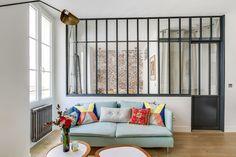 Mélange de styles dans ce 36 m2 : dans le salon un canapé bleu ciel et des coussins multicolores