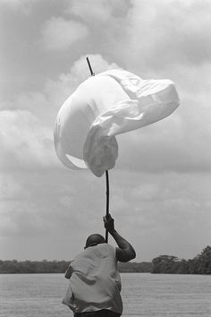 Cinco días después de la tragedia de Bojayá. Clirio sostiene una sábana, convertida en bandera, para solicitarle a los actores armados que no disparen. Río Atrato, Bojayá, Chocó. Mayo 7 de 2002. Jesús Abad.