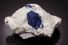 "LAZURITE IN MATRIX  Koksha Valley, Badakhshan Province, Afghanistan   As one of the three components of the semi-precious rock: Lapis Lazuli, the mineral Lazurite is responsible for the intense blue coloration of the same. Although there are several sources worldwide for Lazurite, only the ""classic"" one in Afghanistan produces large, euhedral crystals of this mineral. This one is framed by the colorless, white marble in which it is embedded."