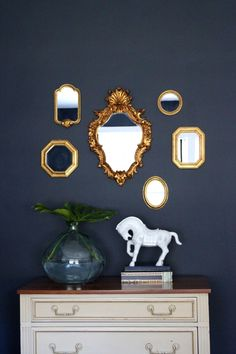 Like this with the Mirrors. Guest Room: Benjamin Moore Hale Navy paint, gold mirror gallery wall, white horse from Homegoods, glass vessel with leaf, cream and gold dresser with maple top.  Love the wall color