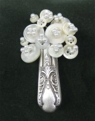 (::)  Repurposed old silverware and shirt buttons  pearls Made into a lapel pin