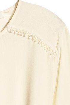 Camicetta con cintura: Camicetta a maniche lunghe in tessuto crêpe con applicazioni in pizzo sulle spalle e a fondo manica. Apertura con bottone sulla nuca, cintura da annodare in vita. Linea arrotondata in basso.